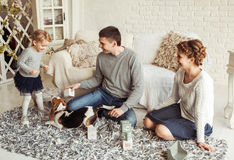 Happy family playing with a pet dog in the spacious living room. Happy parents and five year old daughter playing with a pet dog in the spacious living room on Royalty Free Stock Images