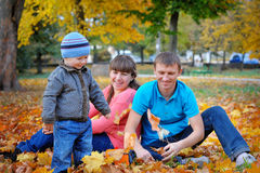 Happy family playing piggyback in autumn park Stock Photo