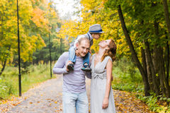 Happy family playing piggyback in autumn park Royalty Free Stock Photos