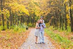 Happy family playing piggyback in autumn park Stock Photos