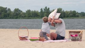 Happy family playing pillows fight on beach Royalty Free Stock Image