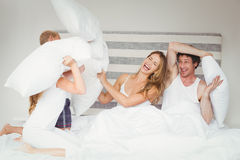 Happy family playing with pillows Stock Images