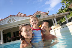 Happy family playing in the pool. Family playing in swimming pool of private villa Royalty Free Stock Images