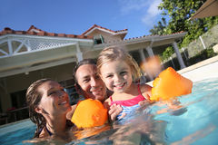 Happy family playing in the pool. Family playing in swimming pool of private villa Stock Image