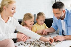 happy family playing with puzzle pieces stock photo