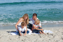 Happy family playing on the sand Stock Image