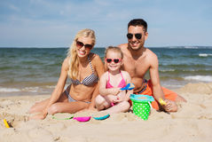 Happy family playing with sand toys on beach Stock Images