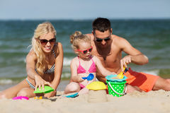 Happy family playing with sand toys on beach Stock Image