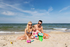 Happy family playing with sand toys on beach Stock Photo