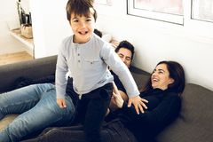 A happy family playing and smiling on the couch at home. Concept of love between parents and children stock photos