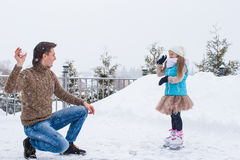 Happy family playing snowballs in winter snowy day Stock Photography