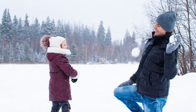 Happy family playing snowballs in winter snowy day Royalty Free Stock Photography