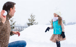 Happy family playing snowballs in winter snowy day Stock Photo