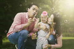 Happy family playing with soap bubbles Royalty Free Stock Photo