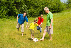 Happy family playing soccer Stock Photography