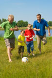 Happy family playing soccer Royalty Free Stock Photos