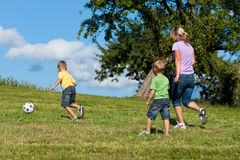 Happy family is playing soccer in summer royalty free stock images