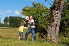 Happy family is playing soccer in summer royalty free stock photography