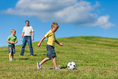 Happy family is playing soccer in summer stock image