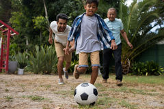 Happy family playing soccer in yard Royalty Free Stock Photography