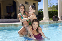 Happy Family Playing In A Swimming Pool. A mother and father having fun on vacation playing with their children on their shoulders in a swimming pool Stock Images