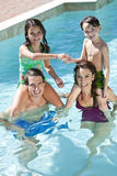 Happy Family Playing In A Swimming Pool. A mother and father having fun on vacation playing with their children on their shoulders in a swimming pool Stock Image