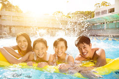 Happy family playing in swimming pool. Happy asian family playing in swimming pool Stock Photography