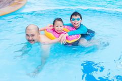 Happy family playing in swimming pool. Happy Asian family playing together in swimming pool Stock Images