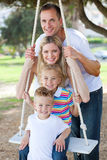 Happy family playing on a swing Stock Images