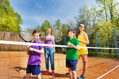 Happy family playing tennis on court Stock Image