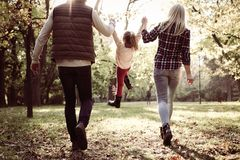 Happy family playing with their daughter in park. royalty free stock photos