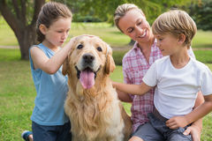 Happy family playing with their dog Royalty Free Stock Photo