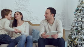 Happy family playing with their son sitting on the sofa while using digital tablet stock footage