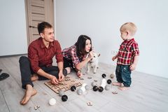 Happy family are playing together on the floor. A mother, father and son are playing together on the floor royalty free stock image