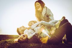 Happy family playing together on grass. stock image