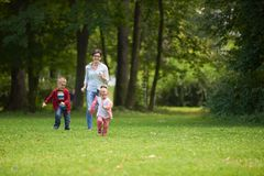 Happy family playing together outdoor in park Stock Photos