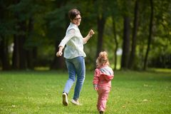 Happy family playing together outdoor in park Stock Images