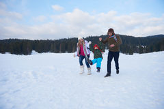 Happy family playing together in snow at winter Royalty Free Stock Photos