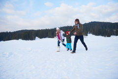 Happy family playing together in snow at winter Royalty Free Stock Photography