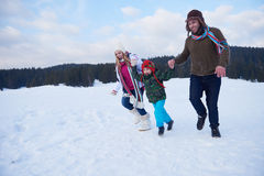Happy family playing together in snow at winter Royalty Free Stock Image
