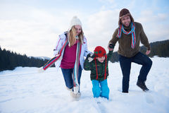 Happy family playing together in snow at winter Stock Photo