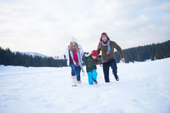 Happy family playing together in snow at winter Stock Image