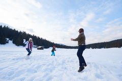 Happy family playing together in snow at winter Stock Images