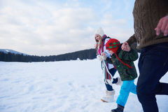 Happy family playing together in snow at winter Stock Photos
