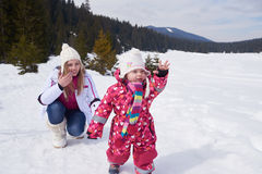 Happy family playing together in snow at winter Royalty Free Stock Images