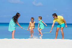 Happy family playing together on white beach Stock Photo