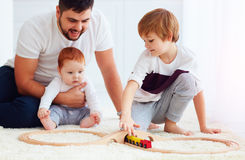 Happy family playing with toy railway road at home Stock Images