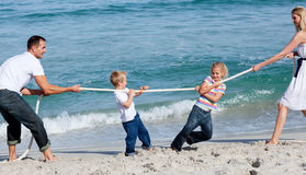 Happy family playing tug of war Stock Photo