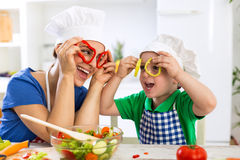 Happy family playing with vegetables in kitchen Stock Photos