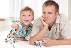 Happy family playing a video game. Happy family - father and child playing a video game Royalty Free Stock Photo